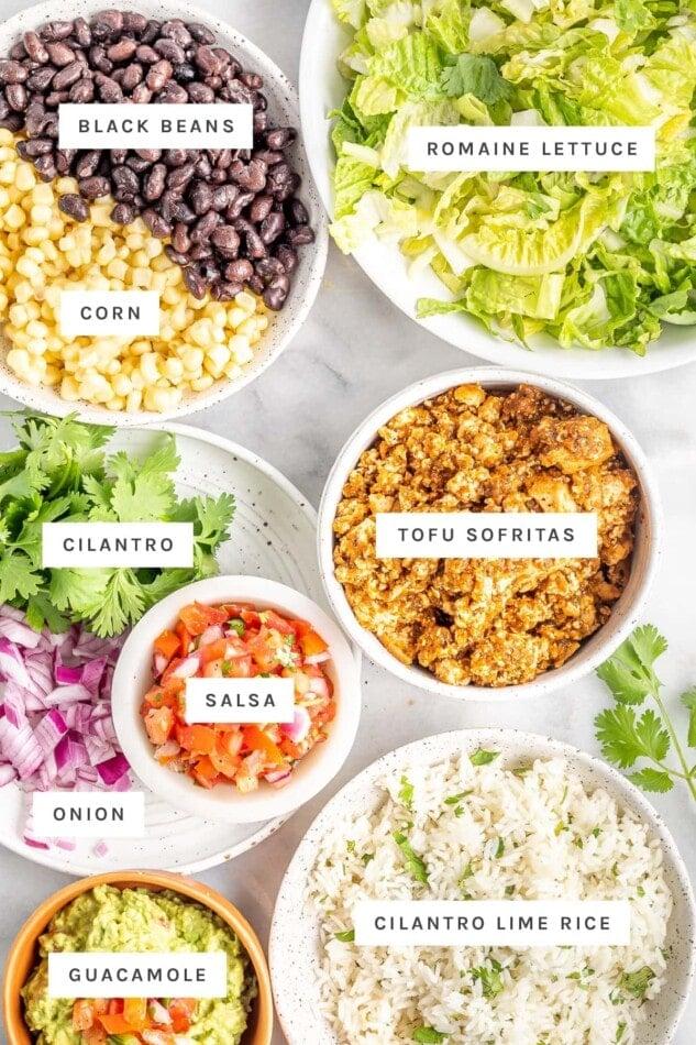 Ingredients measured out to make vegan burrito bowls: black beans, corn, lettuce, tofu sofritas, cilantro, salsa, onion, cilantro lime rice and guacamole.