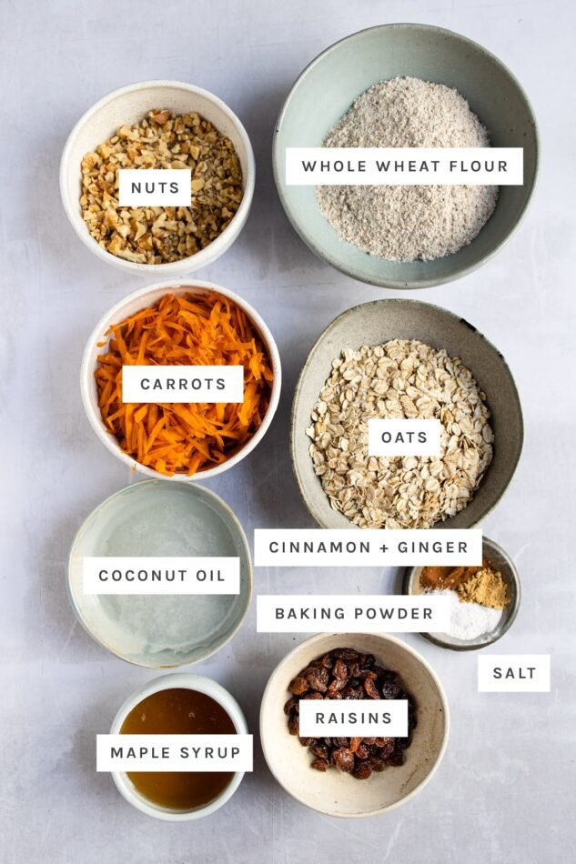 Ingredients measured out to make carrot cake breakfast cookies: nuts, wheat flour, shredded carrots, oats, coconut oil, cinnamon, ginger, baking powder, salt, maple syrup and raisins.