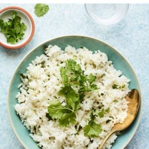 Bowl of cilantro rice with a serving spoon.