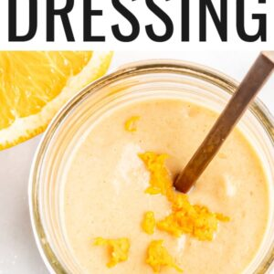 Jar of citrus tahini dressing with a spoon and topped with orange zest.