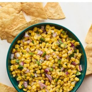 Bowl of corn salsa surrounded by tortilla chips.