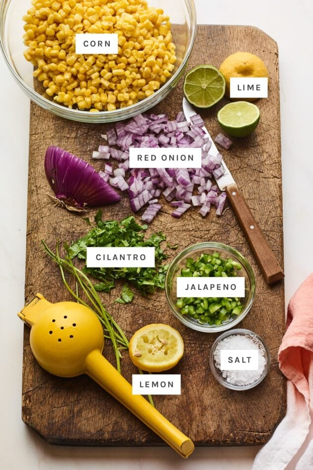 Ingredients measured out to make corn salsa: corn, lime, onion, cilantro, jalapeno, lemon and salt.