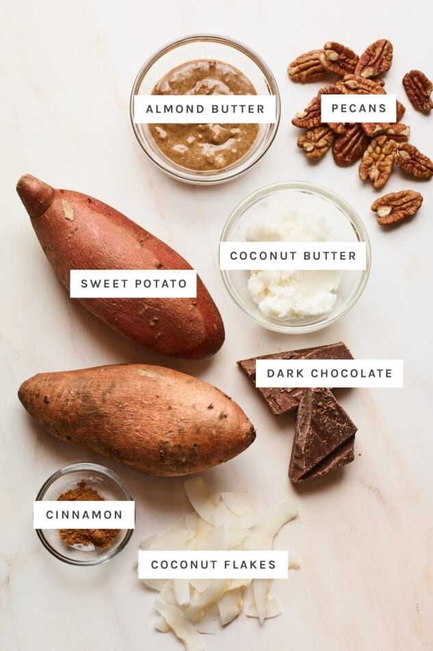 Ingredients measured out to make dessert baked sweet potatoes: almond butter, pecans, coconut butter, sweet potatoes, dark chocolate, cinnamon and coconut flakes.