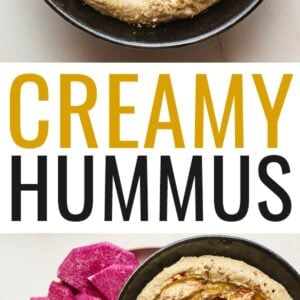 Creamy hummus with olive and spices on top in a black serving bowl with sliced vegetables for dipping plated around the bowl.