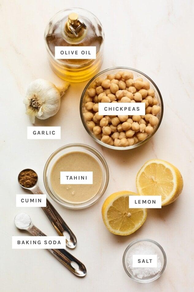 Ingredients measured out to make hummus: olive oil, chickpeas, garlic, tahini, lemon, cumin, baking soda and salt.