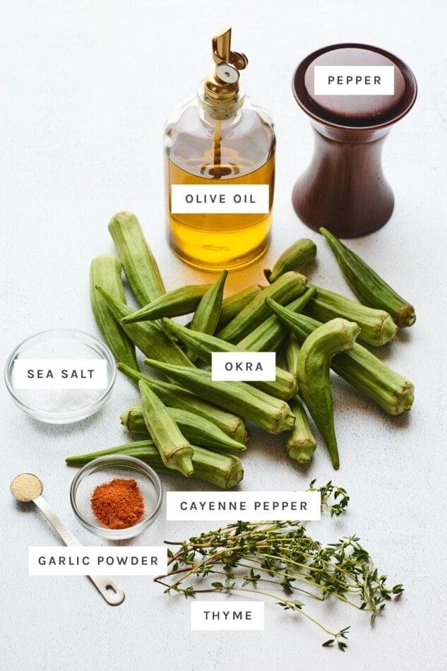 Ingredients measured out to make roasted okra: olive oil, pepper, salt, fresh okra, garlic powder, cayenne pepper and fresh thyme.