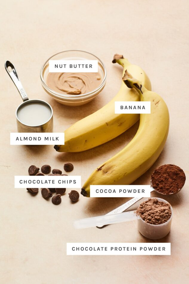 Ingredients measured out to make chocolate protein ice cream: nut butter, banana, almond milk, cocoa powder, chocolate protein powder and chocolate chips.