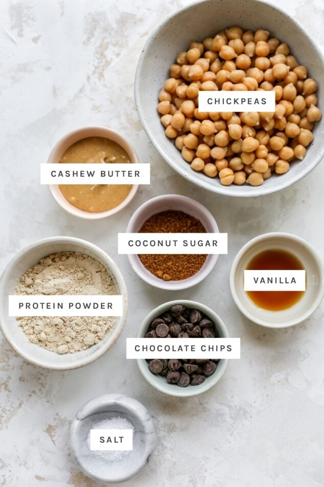 Ingredients measured out to make protein cookie dough: chickpeas, cashew butter, coconut sugar, vanilla, protein powder, chocolate chips and salt.