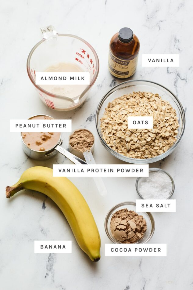 Ingredients measured out to make no bake protein cookies: almond milk, vanilla, oats, peanut butter, protein powder, oats, banana, salt and cocoa powder.