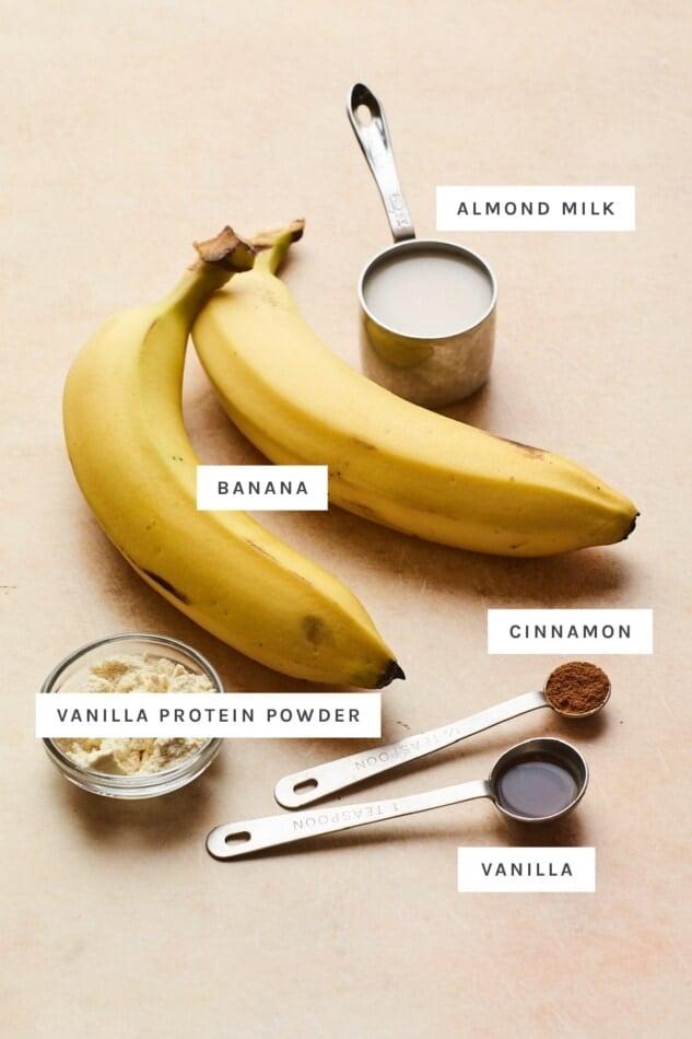 Ingredients measured out to make vanilla protein ice cream: almond milk, banana, cinnamon, protein powder and vanilla.