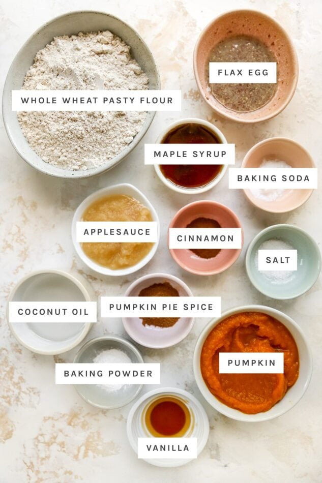 Ingredients measured out in little bowls to make pumpkin bread: whole wheat pastry flour, flax egg, maple syrup, baking soda, applesauce, cinnamon, salt, coconut oil, pumpkin pie spice, baking powder, pumpkin and vanilla.
