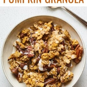 A bowl of pumpkin granola served in a bowl with milk. A silver spoon rests aside the bowl.