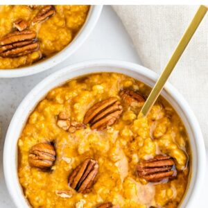 Bowl of pumpkin oatmeal topped with pecans and maple syrup.