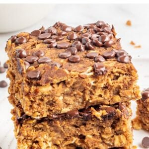 A stack of protein pumpkin bars on a white plate with chocolate chips sprinkled around.