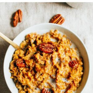 Bowl of pumpkin pie oatmeal topped with almond milk and pecans.