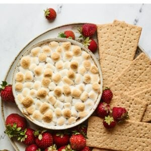 S'mores dip plated with strawberries and graham crackers for dipping.