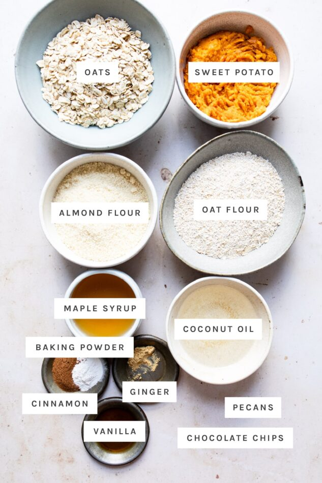 Ingredients measured out in bowls to make sweet potato breakfast cookies: oats, sweet potato, almond flour, oat flour, maple syrup, coconut oil, baking powder, cinnamon, ginger, vanilla, pecans and chocolate chips.