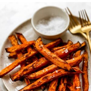 A plate of air fryer sweet potato fries with two forks and a ramekin of salt.