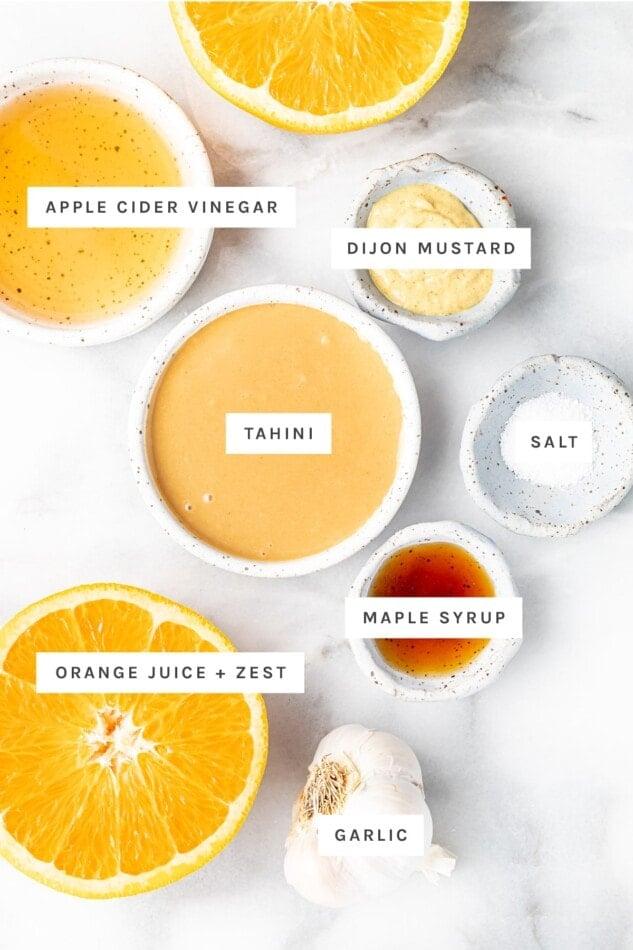 Ingredients measured out to make citrus tahini dressing: apple cider vinegar, dijon mustard, tahini, salt, maple syrup, orange juice and zest and garlic.