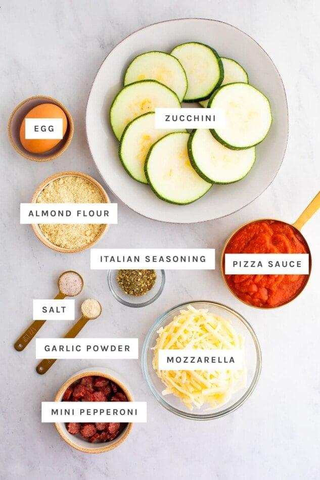 Ingredients measured out to make zucchini pizza bites: egg, zucchini, almond flour, Italian seasoning, pizza sauce, salt, garlic powder, mozzarella and a pepperoni stick.