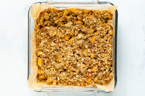 A glass baking pan lined with parchment paper and filled with apple crumble filling before being baked.