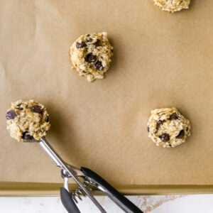 A sheet pan lined with parchment paper with cookies scooped onto it. There is a cookie scoop resting on the sheet pan.