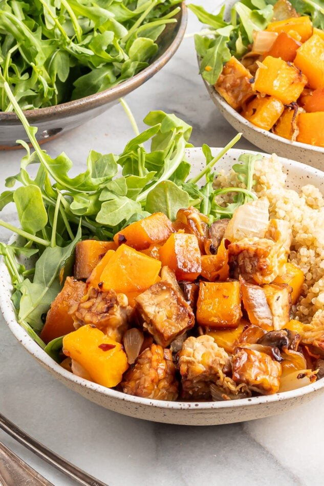 A shallow bowl filled with butternut squash tempeh bake served with brown rice and greens.