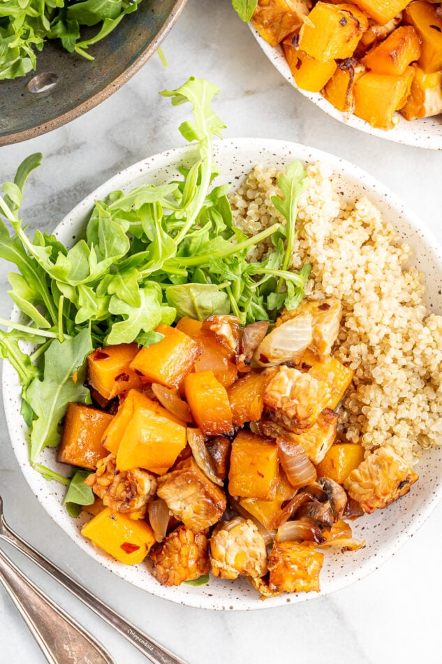 Butternut squash tempeh bake served with brown rice and greens in a shallow bowl.
