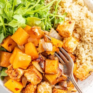 Overhead view of butternut squash tempeh bake served with brown rice and greens, a fork is scooping a bite.