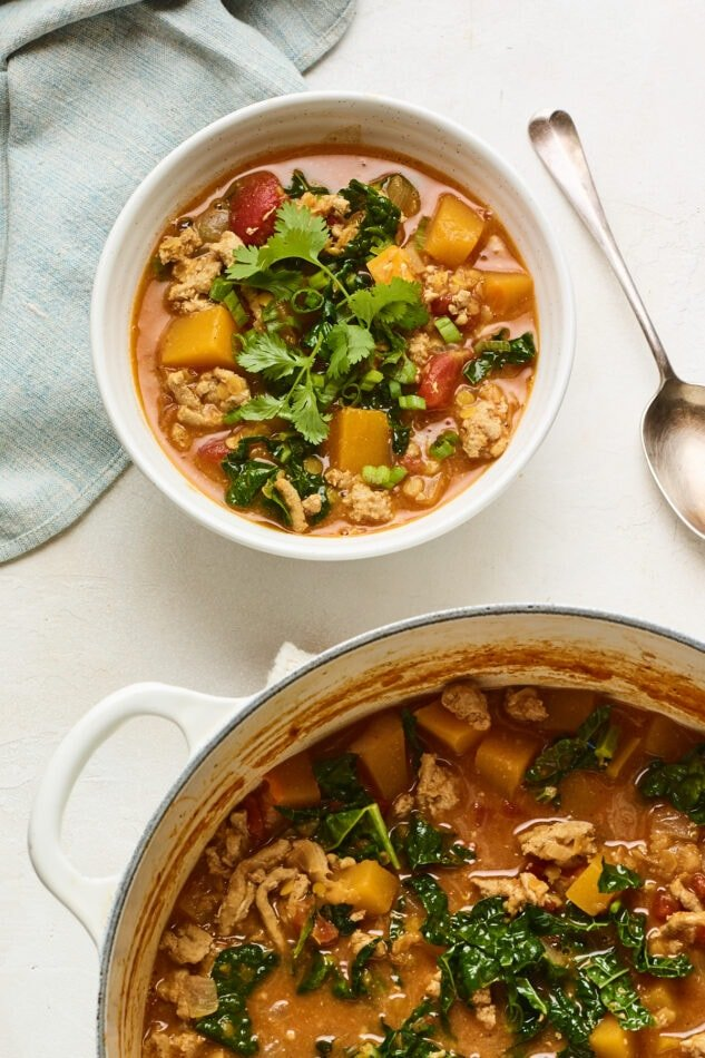 A bowl of butternut squash turkey chili topped with cilantro. A serving pot of chili is cut halfway out of frame.