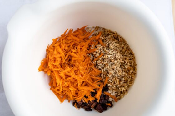 A bowl containing carrots, pecans, and raisins ready to be combined.