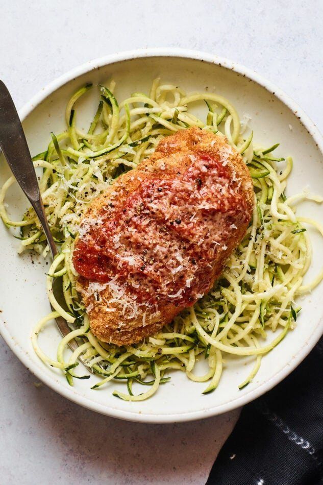 An overhead shot of a bowl zucchini noodles with a chicken parm breast resting on top. A fork rests inside the bowl.