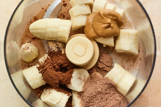 Banana, cocoa powder, chocolate protein powder, peanut butter and almond milk in a food processor.