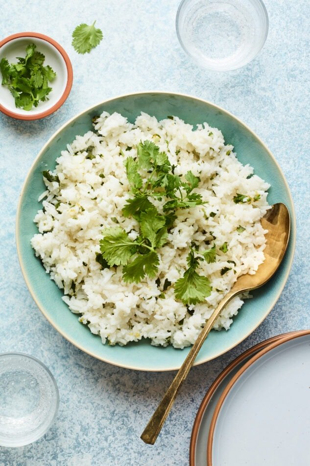Overhead shot of a bowl of cilantro rice with a serving spoon.