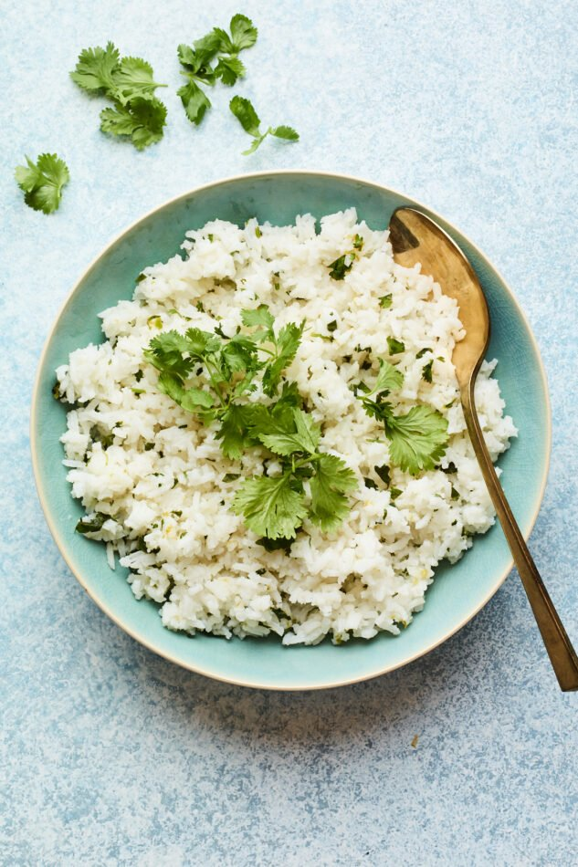 Overhead shot of easy cilantro rice in a serving bowl with a serving spoon.