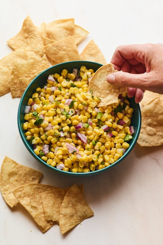 Hand dipping tortilla chip into bowl of easy corn salsa served in blue bowl.