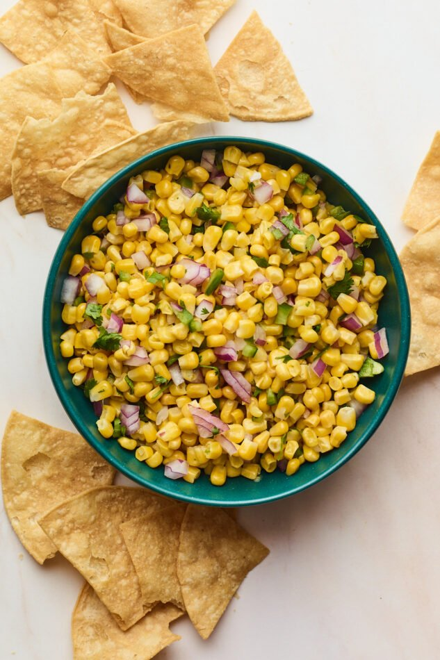 Easy corn salsa served in a blue bowl with crispy tortilla chips scattered around the bowl.