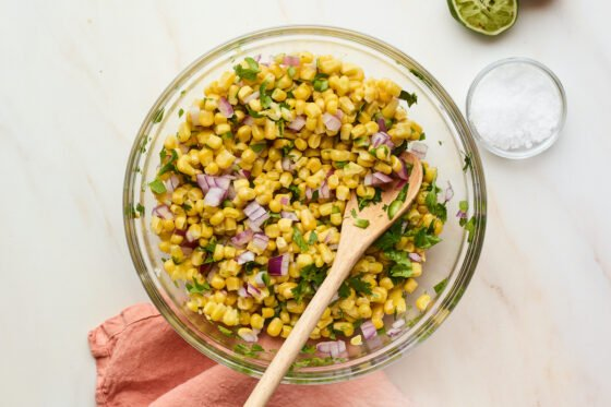 Corn salsa in glass mixing bowl with wooden mixing spoon.
