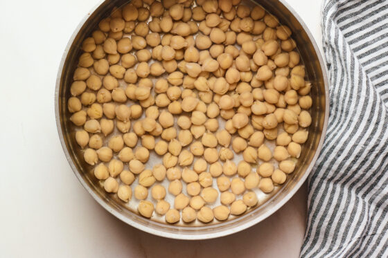 Chickpeas soaking in water in a sauce pan.
