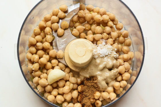 Chickpeas, tahini, garlic, salt, lemon juice, and olive oil in a food processor ready to be blended.
