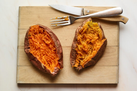 A wooden cutting board with two baked sweet potatoes on top. The sweet potatoes have been sliced open with the insides mashed. There is a fork and knife resting on the cutting board.