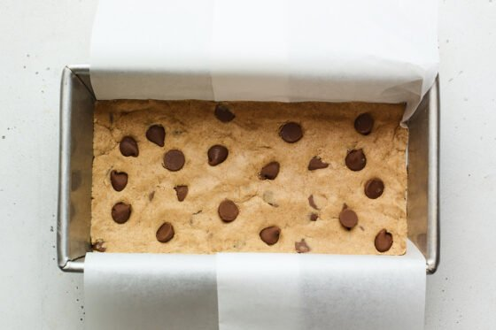 Chocolate chip peanut butter protein bar mixture in a loaf pan lined with parchment.