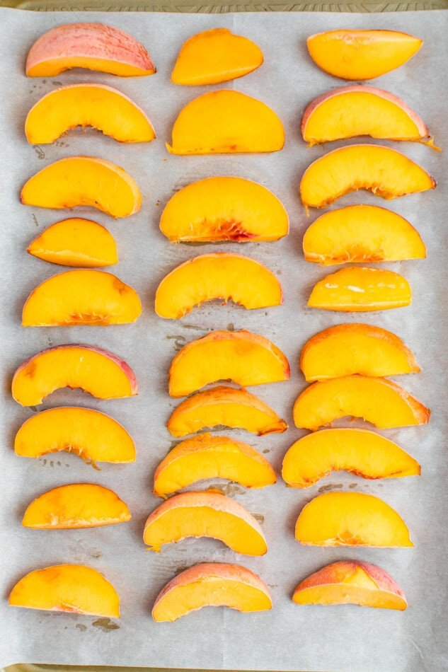 Frozen peaches in three columns on a parchment lined baking sheet