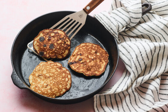 Cast iron skillet with three protein pancakes and a spatula lifting one up.
