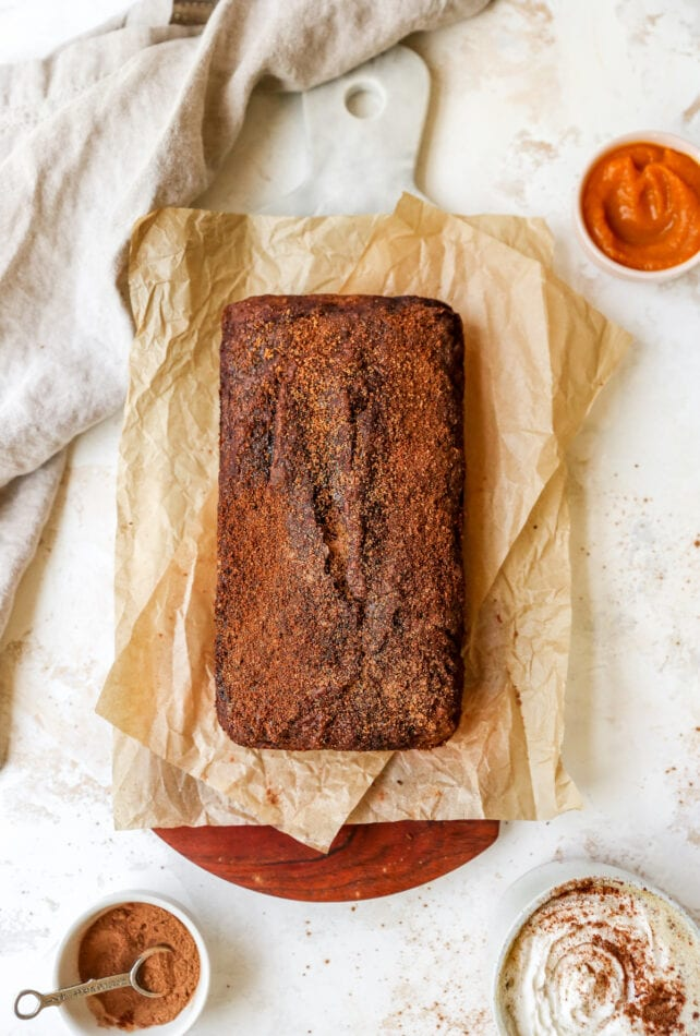 An overhead shot of a loaf of pumpkin bread, resting on parchment paper on top of a cutting board. Several ingredients in small dishes are scattered around the loaf of bread.