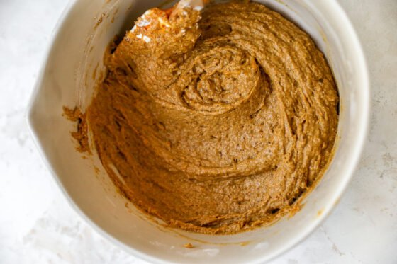 A bowl with the ingredients for pumpkin bread all mixed together.