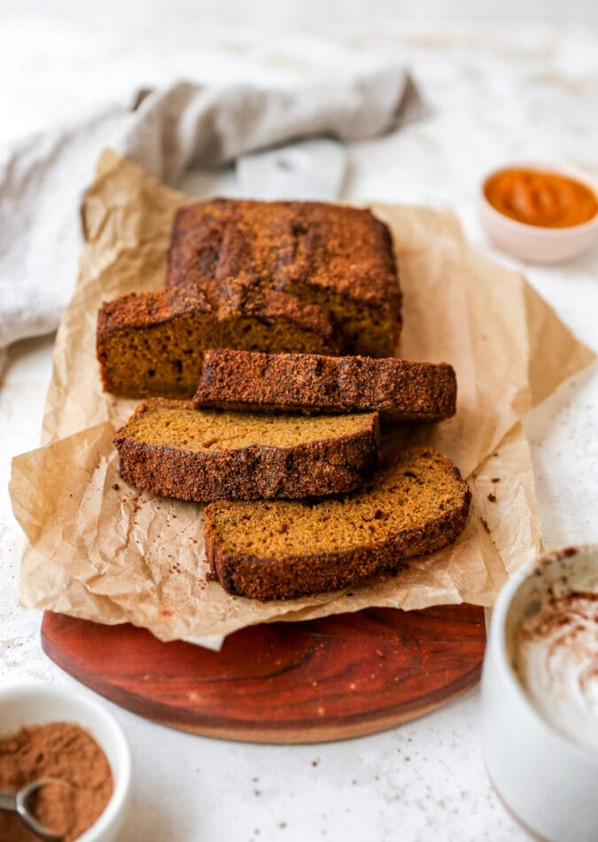 Loaf of pumpkin bread on a parchment paper resting on a cutting board. 4 slices have been cut from the loaf.