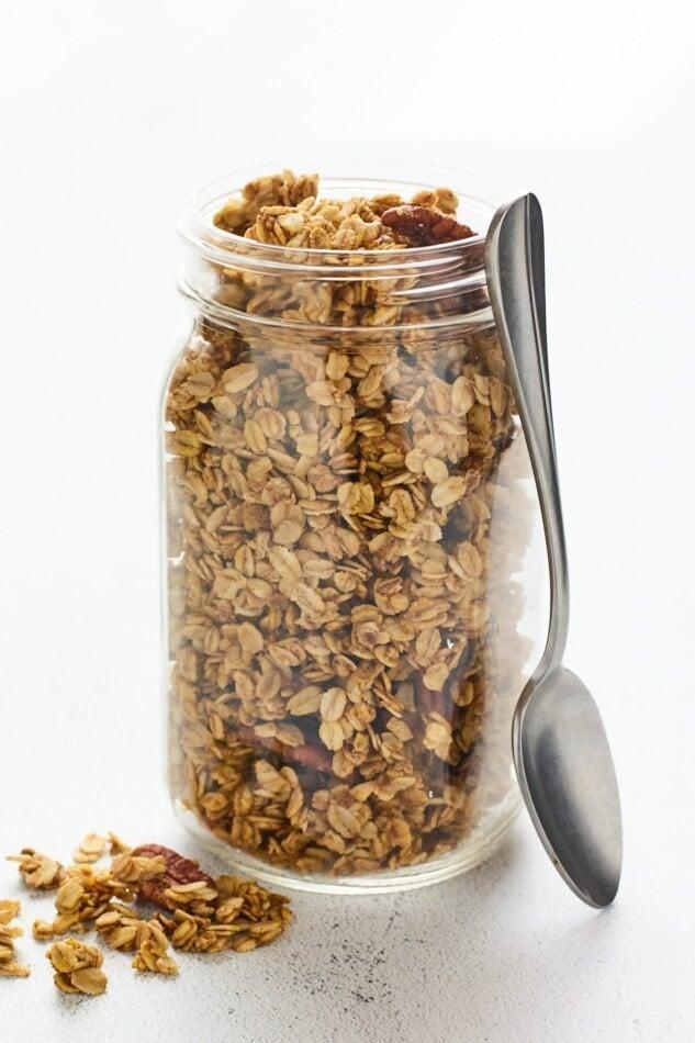 A mason jar filled with pumpkin granola. A silver spoon rests alongside the jar.