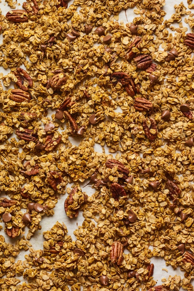 Sheet pan of baked pumpkin granola with melted chocolate chips sprinkled throughout.