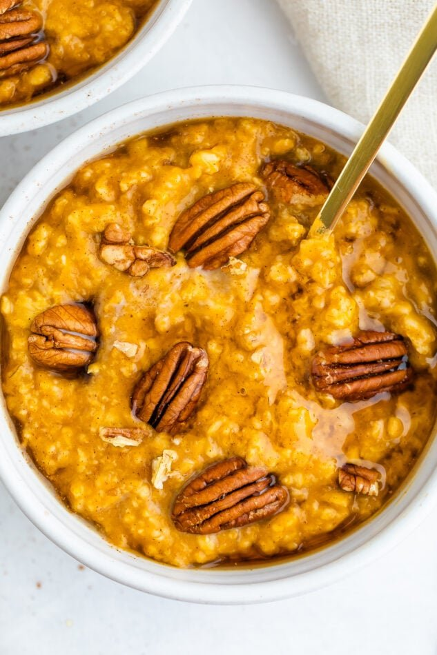 Close up shot of pumpkin oatmeal in a white bowl topped with whole pecans.